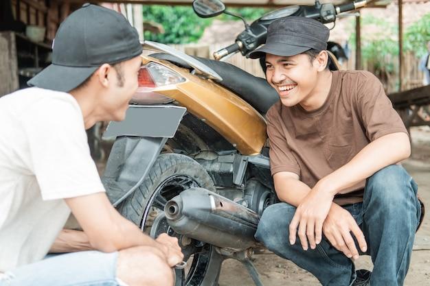 Asiatischer mann lächelt einen reifenmechaniker an, nachdem er einen undichten motorradreifen in der werkstatt repariert hat