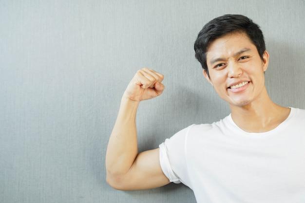 Asiatischer mann lächelt mit dem zeigen des bizepsunterarms zur guten gesundheit und zum starken körperkonzept