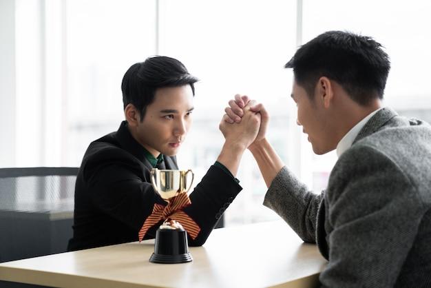 Asiatischer mann mit armdrücken mit trophäenwettbewerb / geschäftswettbewerb / gewinner