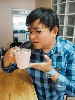 Asiatischer mann mit brille im blauen hemd trinkt latte-kaffee am holztisch, macht eine pause von der arbeit