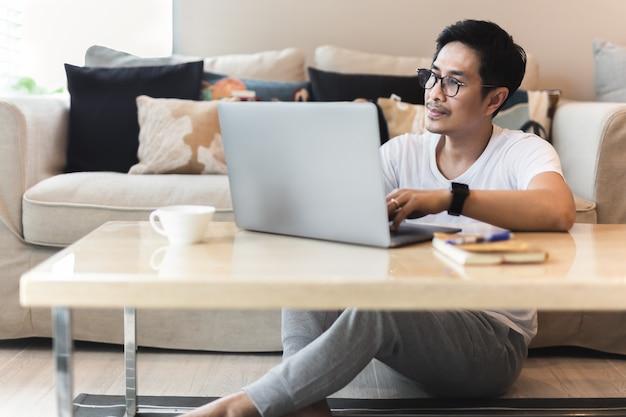 Asiatischer mann mit brille sitzt auf dem boden mit laptop zu hause
