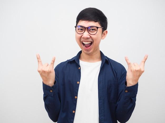 Asiatischer mann mit brille zeigt handrocker, der sich glücklich schreit