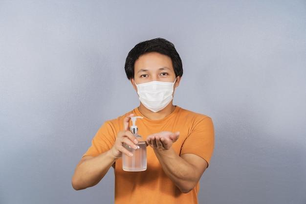 Asiatischer mann mit chirurgischer gesichtsmaske, der alkoholgel oder händedesinfektionsmittel präsentiert und verwendet