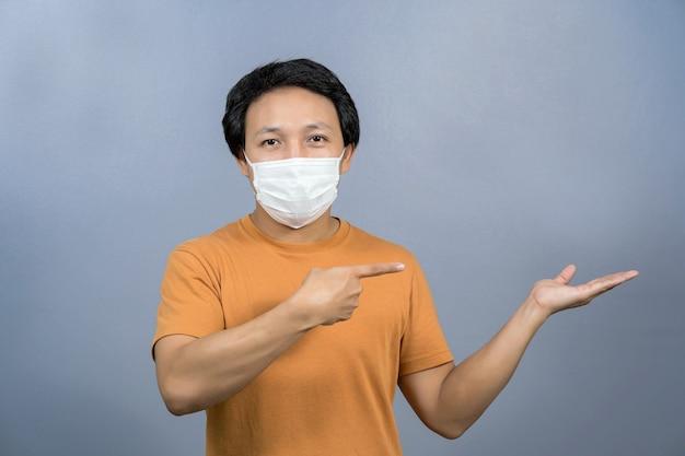 Asiatischer mann mit chirurgischer gesichtsmaske, der ein produkt über coronavirus zeigt und präsentiert