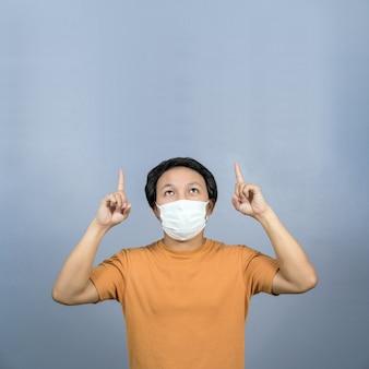 Asiatischer mann mit chirurgischer gesichtsmaske, der ein produkt zeigt und präsentiert