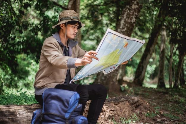 Asiatischer mann mit der karte und hut, welche die karte sitzen und sehen