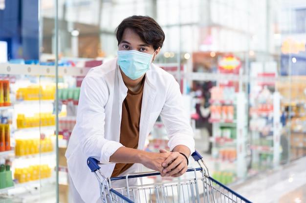 Asiatischer mann mit der medizinischen gesichtsmaske, die bei suppermaket einkauft