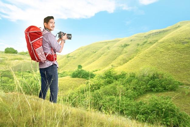 Asiatischer mann mit einem rucksack, der eine kamera hält, um fotos zu machen