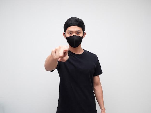 Asiatischer mann mit ernstem gesicht der maske und zeigefinger auf sie weißen hintergrund