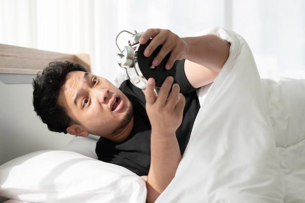 Asiatischer mann mit geschocktem gesicht nach dem späten aufwachen und verpasste den termin