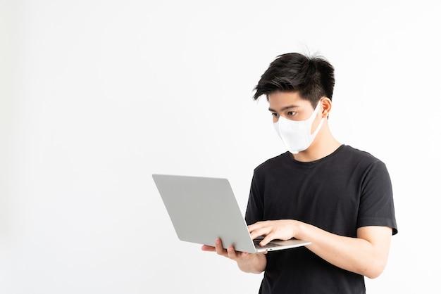 Asiatischer mann mit gesichtsmaske zum schutz von coronavirus covid-19 mit einem laptop im quarantäneraum. quarantäne selbst zum schutz von verbreitetem covid-19 coronavirus