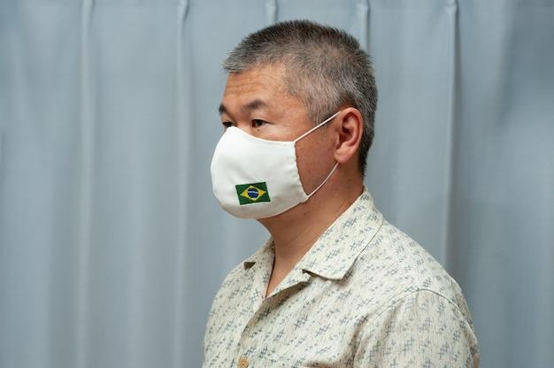 Asiatischer mann mit hausgemachter stoffmaske mit brasilianischer flagge zum schutz vor coronavirus