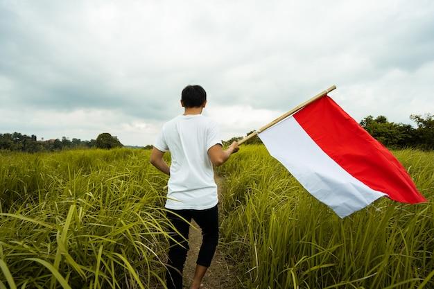 Asiatischer mann mit indonesischer flagge von indonesien oben auf dem berg