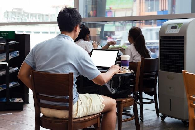 Asiatischer mann mit laptop mit leerem bildschirm am tisch im café drinnen sitzend