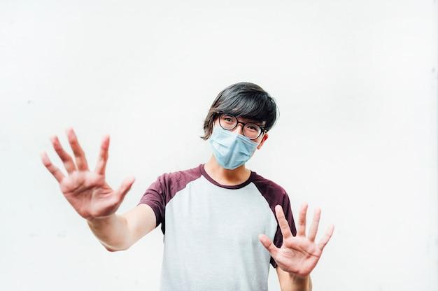 Asiatischer mann mit maske und brille mit seinen händen vorne