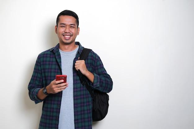 Asiatischer mann mit rucksack, der glücklich ist, während er sein handy hält?