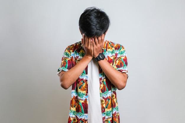 Asiatischer mann mit schnurrbart, der ein lässiges hemd mit traurigem ausdruck trägt und das gesicht mit den händen bedeckt, während er weint. depression-konzept auf weißem hintergrund