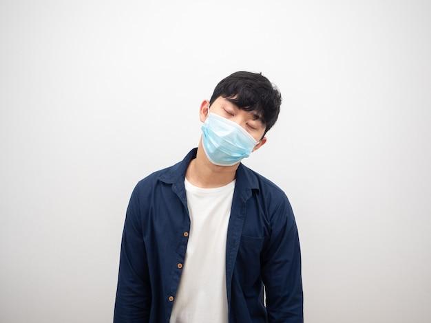 Asiatischer mann mit schutzmaske krank und geschlossenen augen fühlen sich auf weißem hintergrund schlecht