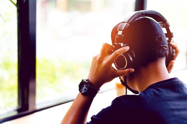 Asiatischer mann mit schwarzem hemd freiberufler haben spaß beim arbeiten an ihren schreibtischen und beim musikhören über kopfhörer. entspannungskonzept