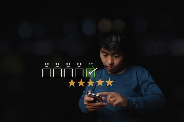 Asiatischer mann mit smartphone mit virtuellem bildschirm auf dem smiley-symbol auf dem digitalen touchscreen. bewertungskonzept für den kundenservice.
