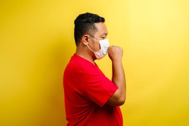 Asiatischer mann mit stoffmaske, der an husten leidet, isoliert auf gelbem hintergrund