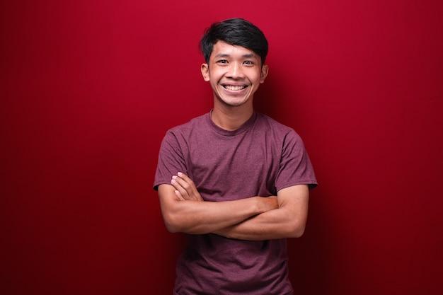 Asiatischer mann mit verschränkten armen und freut sich auf rotem hintergrund