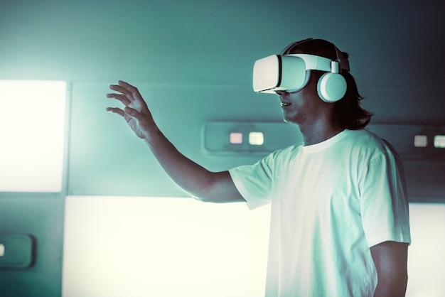 Asiatischer mann mit vr-headset, der einen virtuellen bildschirm berührt