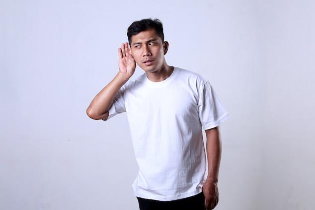Asiatischer mann mit weißem t-shirt mit hörendem ausdruck auf weißem hintergrund
