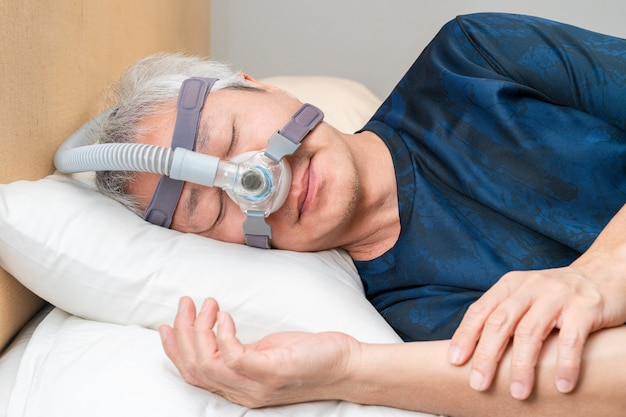 Asiatischer mann mittleren alters, der cpap-kopfbedeckung während seines schlafes trägt