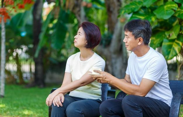 Asiatischer mann mittleren alters, der darum bittet, sich mit seiner frau zu versöhnen