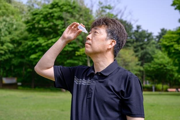 Asiatischer mann mittleren alters, der draußen augentropfen in die augen setzt.