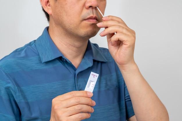 Asiatischer mann mittleren alters, der mit covid-19-heim-antigen-kits auf coronavirus getestet wurde.