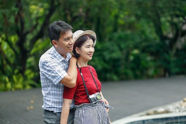 Asiatischer mann mittleren alters, der sich mit seiner frau am hochzeitstag entspannt?