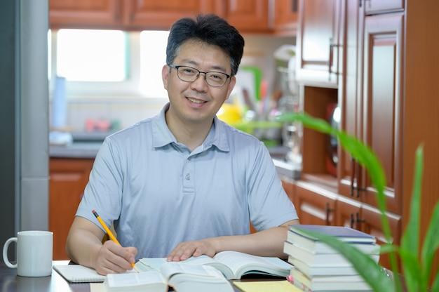 Asiatischer mann mittleren alters, der zu hause am schreibtisch sitzt, ein buch liest und studiert.