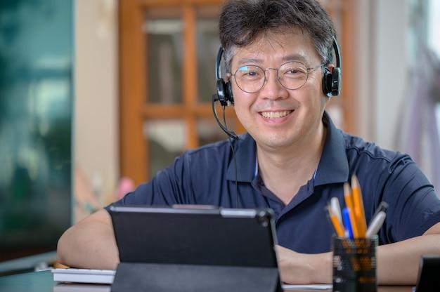 Asiatischer mann mittleren alters, der zu hause arbeitet. telearbeitskonzept.