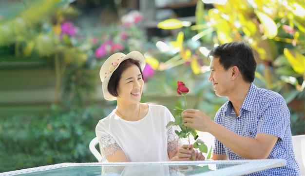 Asiatischer mann mittleren alters gibt seiner frau eine rose