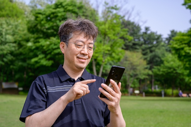 Asiatischer mann mittleren alters mit einem smartphone auf dem rasen.