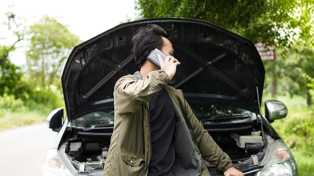Asiatischer mann öffnete die motorhaube des autos, während er anrief