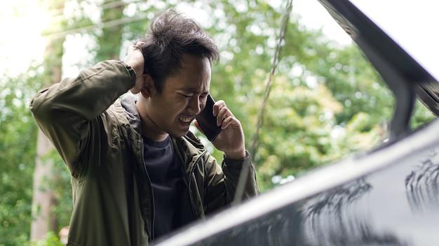 Asiatischer mann öffnete die motorhaube des autos, während er während des anrufs verwirrt war