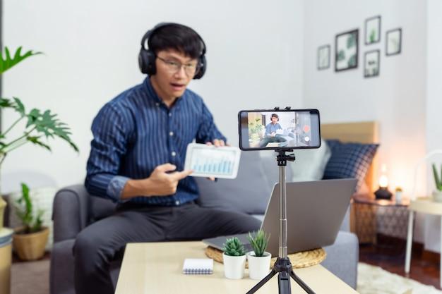Asiatischer mann online-influencer, der video-live-streaming aufzeichnet, mit digitaler smartphone-kamera präsentieren produktbewertung für thema über video-blogging fokus auf kamera-bildschirm-show in den sozialen medien.