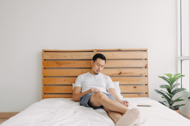 Asiatischer mann schläft mit dem telefon in der hand auf dem bett ein