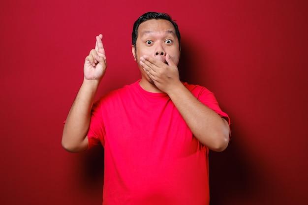 Asiatischer mann schließt seinen mund und kreuzt die finger und macht eine versprechensgeste auf rotem hintergrund