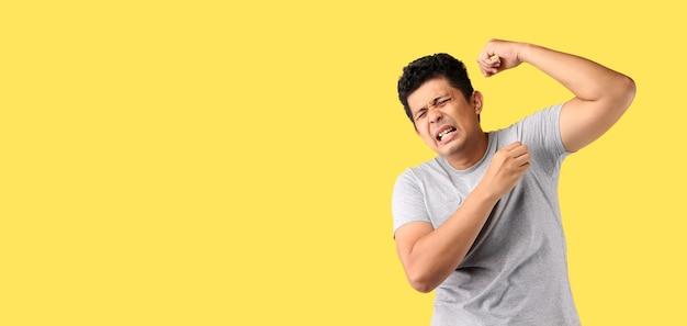 Asiatischer mann schwitzt übermäßig riechend schlecht auf gelb isoliert