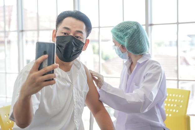 Asiatischer mann selfie per telefon, während er im krankenhaus einen covid-impfstoff bekommt, während die handkrankenschwester den impfstoff injiziert