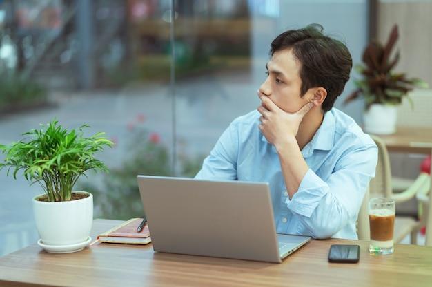 Asiatischer mann sitzt allein arbeitend an einem kaffeegeschäft