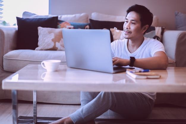 Asiatischer mann sitzt auf dem boden und arbeitet zu hause am laptop