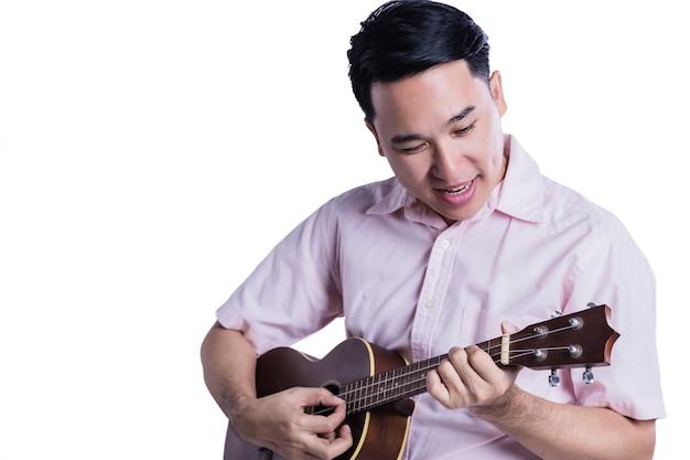 Asiatischer mann spielen ukulele mit glück auf weißem hintergrund