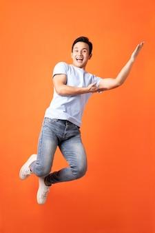 Asiatischer mann springt und zeigt