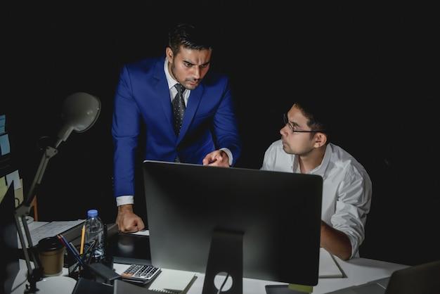 Asiatischer mann supervisor, der personal während der nachtschichtarbeit schuldet
