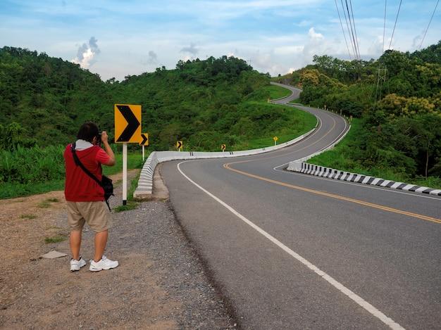 Asiatischer mann tourist, der ein foto auf drei kurvenförmigen straßen auf grünem bergwald in nan, thailand macht?